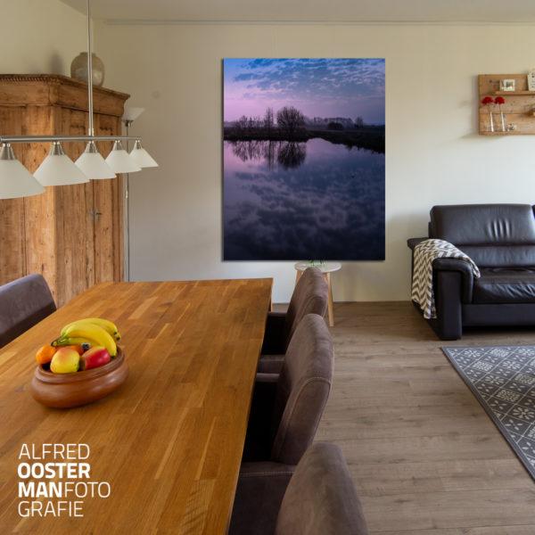 Een foto uit de serie Onlanden van Alfred Oosterman hangt groot aan de wand in een woonkamer.