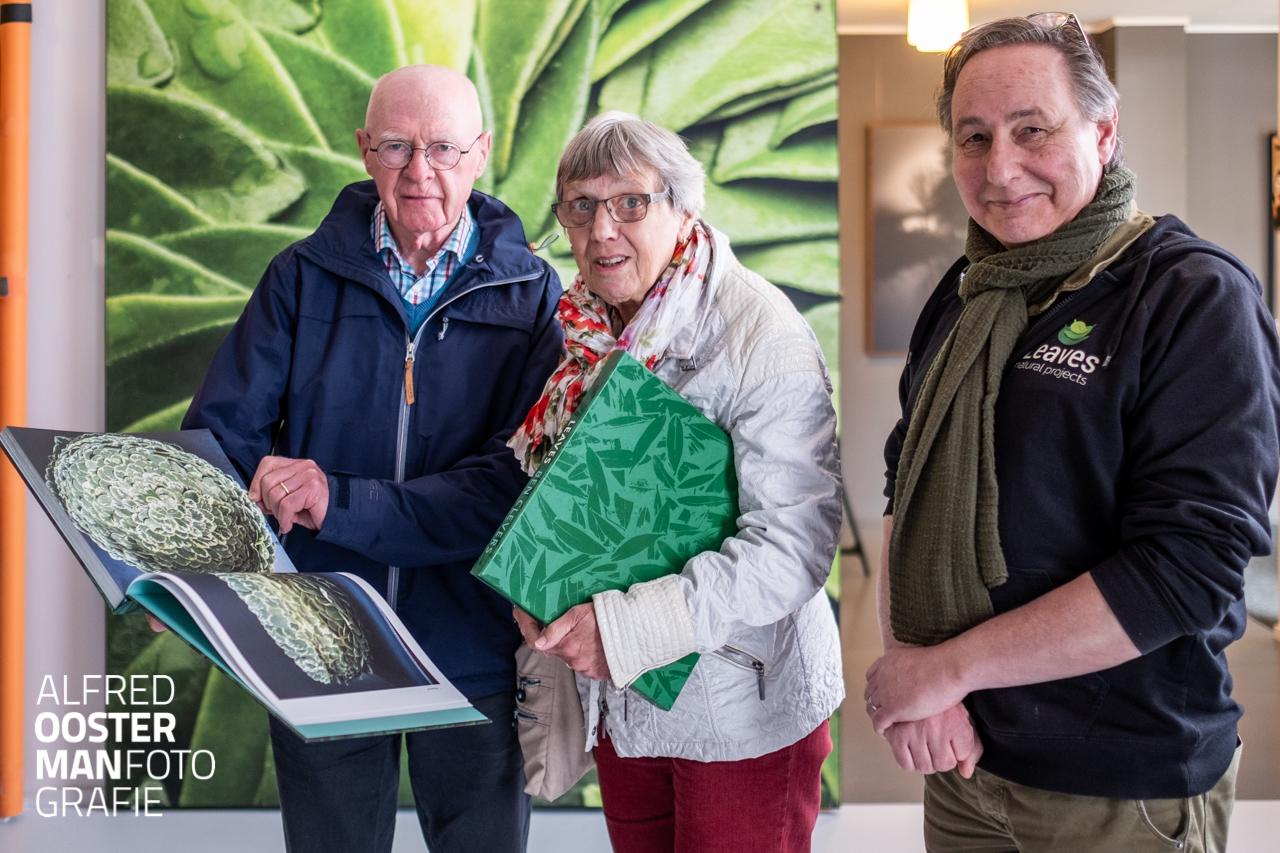 Herman en Paula Oosterman ontvangen het boek Leaves met foedraal uit handen van Ben Clevers