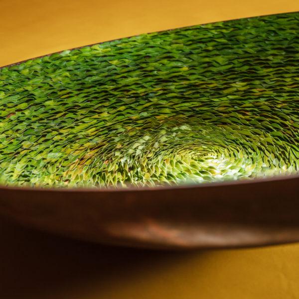 Om dit bladobject, een grote schaal ingelegd met buxusblad, te maken moet je beschikken over enorm veel geduld en doorzettingsvermogen. Blad voor blad is dit object gemaakt en het is indrukwekkend hoe dit bladobject van Ben Clevers er in werkelijkheid uitziet. De combinatie van de kleur van het blad met de schaal en de achtergrond maken het tot een blikvanger aan de muur.