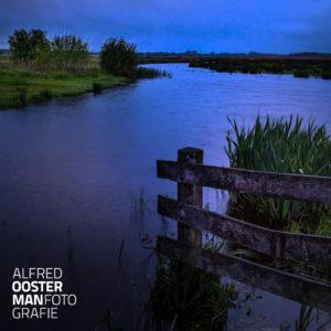 Een winderige en regenachtige ochtend maken het landschap rondom het Eelderdiep nog wat ruiger. Het water staat hoog en stroomt gestaag onder de brug door.
