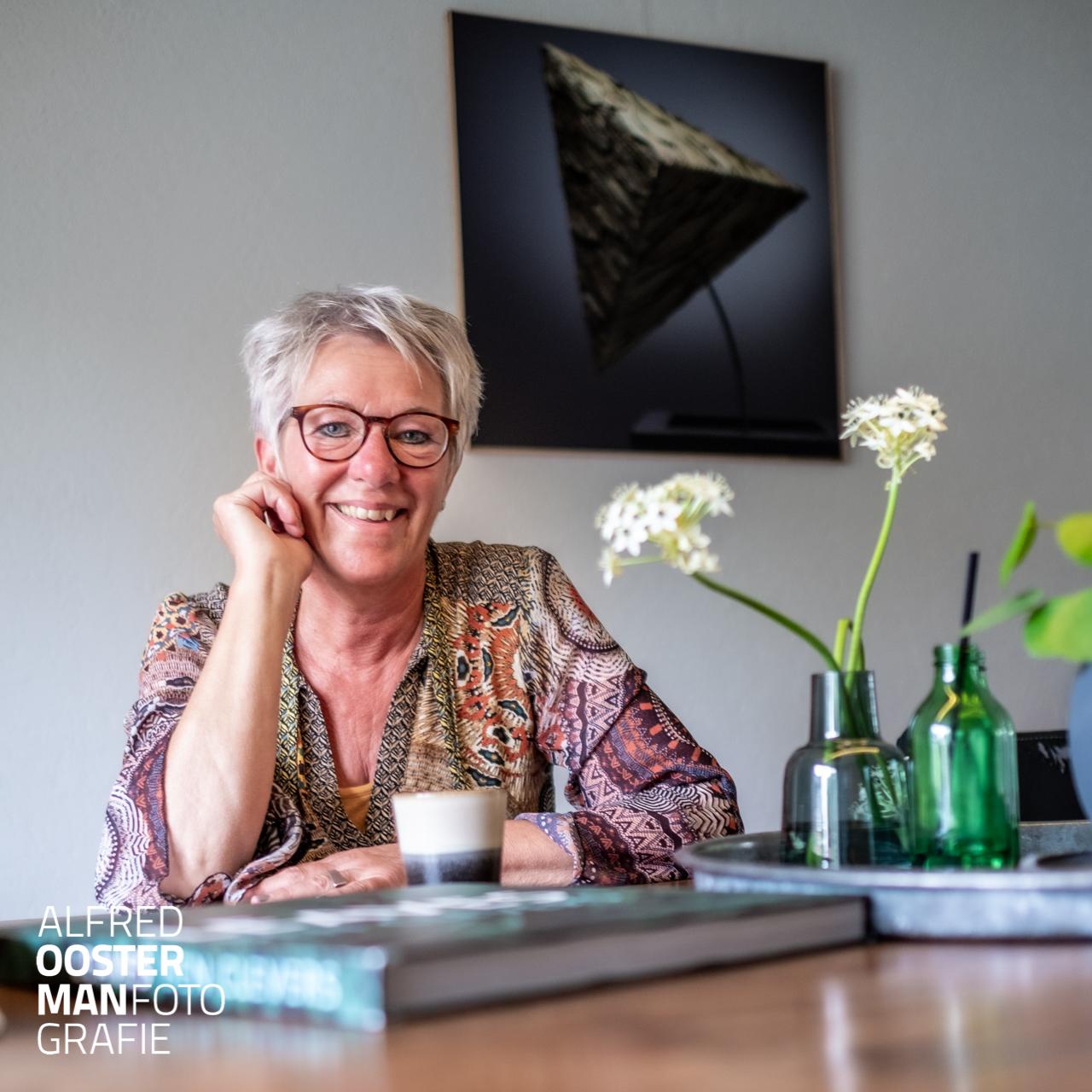Anita Hoekstra met op de achtergrond aan de wand een afbeelding uit het boek Leaves.